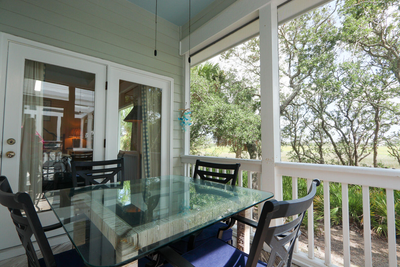 Screened in porch off of living and dining area overlooking marsh