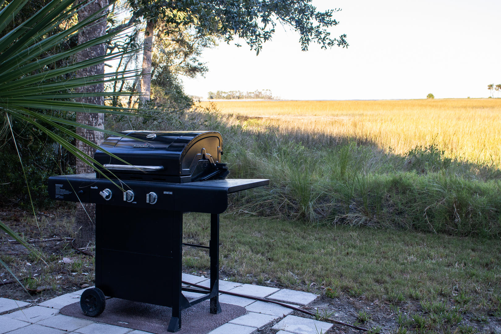 Grill on ground level beneath back deck