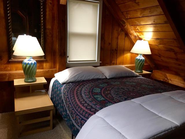 Second floor guest room is open to the sitting area below